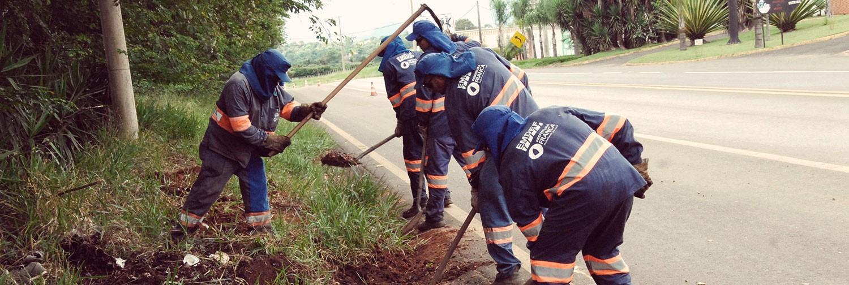 Na foto do banner, funcionários da EMDEF realizando o trabalho de manutenção de vias.