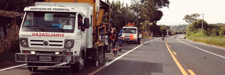Na foto do banner, caminhões de serviço da EMDEF estão estacionados a margem de uma via enquanto funcionários sinalizam com cones de sinalização o local onde será realizado serviços de manutenção.