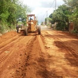 Na foto, uma rua com chão de terra e maquinários da EMDEF trabalhando no local