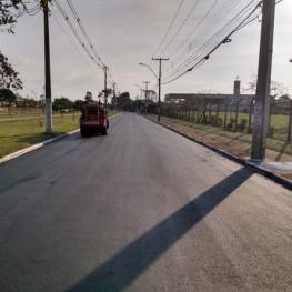 Na foto, uma rua recém recapeada pela EMDEF, ao fundo maquinário utilizado no recapeamento