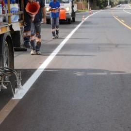Na foto, destaque para  equipamento realizando sinalização de solo em rodovia.