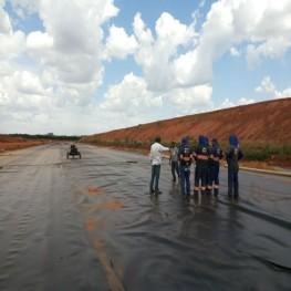 Na foto funcionários inspecionando a aplicação de mante de cobertura sobre o solo.