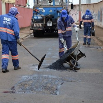 Na imagem, dois funcionários alisando dois novos remendos no asfalto da via onde se encontram Ao fundo, um terceiro funcionário com uma máquina operadora de cor azul.