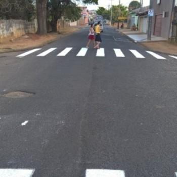 Rua asfaltada e recém sinalizada com duas faixas de pedestre (brancas), uma à frente e outra ao fundo da imagem, onde há duas pessoas atravessando a sinalização.