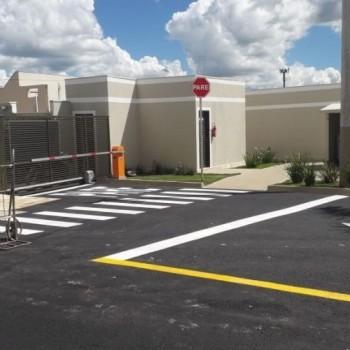 Na imagem, um estacionamento de condomínio sinalizado pela EMDEF, onde há, em frente ao portão de entrada, os dizeres