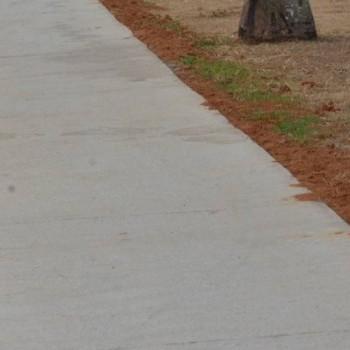 A foto mostra uma calçada recém construída, com concreto novo em cor clara, formando uma linha reta contínua pela calçada. Ao redor, há terra e grama.