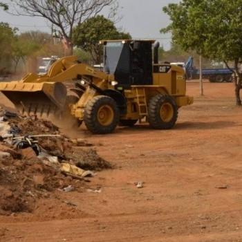 A foto mostra um trator tipo pá carregadeira, de cor amarela, limpando entulho numa área. Ao fundo há outros caminhões, e algumas árvores. Mostra ainda o solo em terra marrom já limpo, após retirada do entulho.